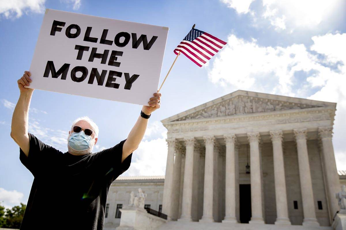 Bill Christeson holds up a sign outside the Supreme Court, Thursday, July 9, 2020, in Washingto ...