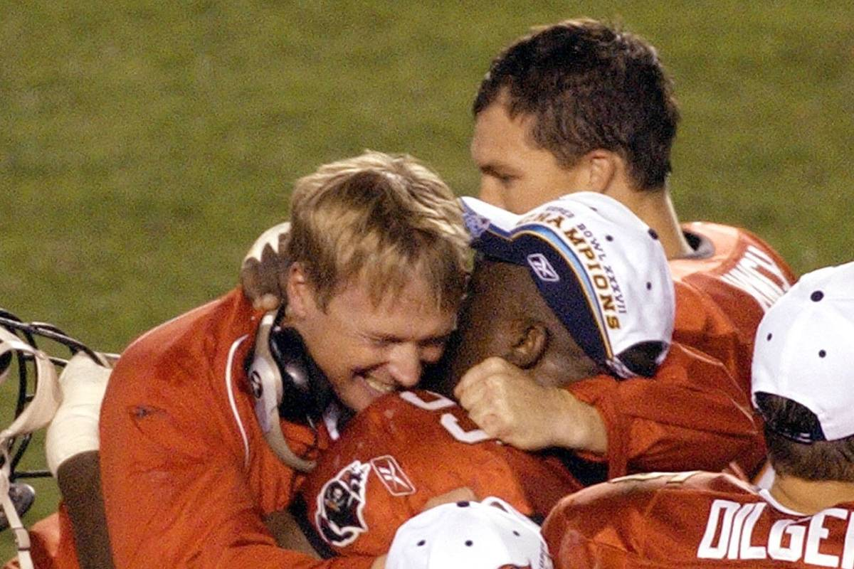 Tampa Bay Buccaneers coach Jon Gruden, left, hugs defensive lineman Warren Sapp as the game aga ...