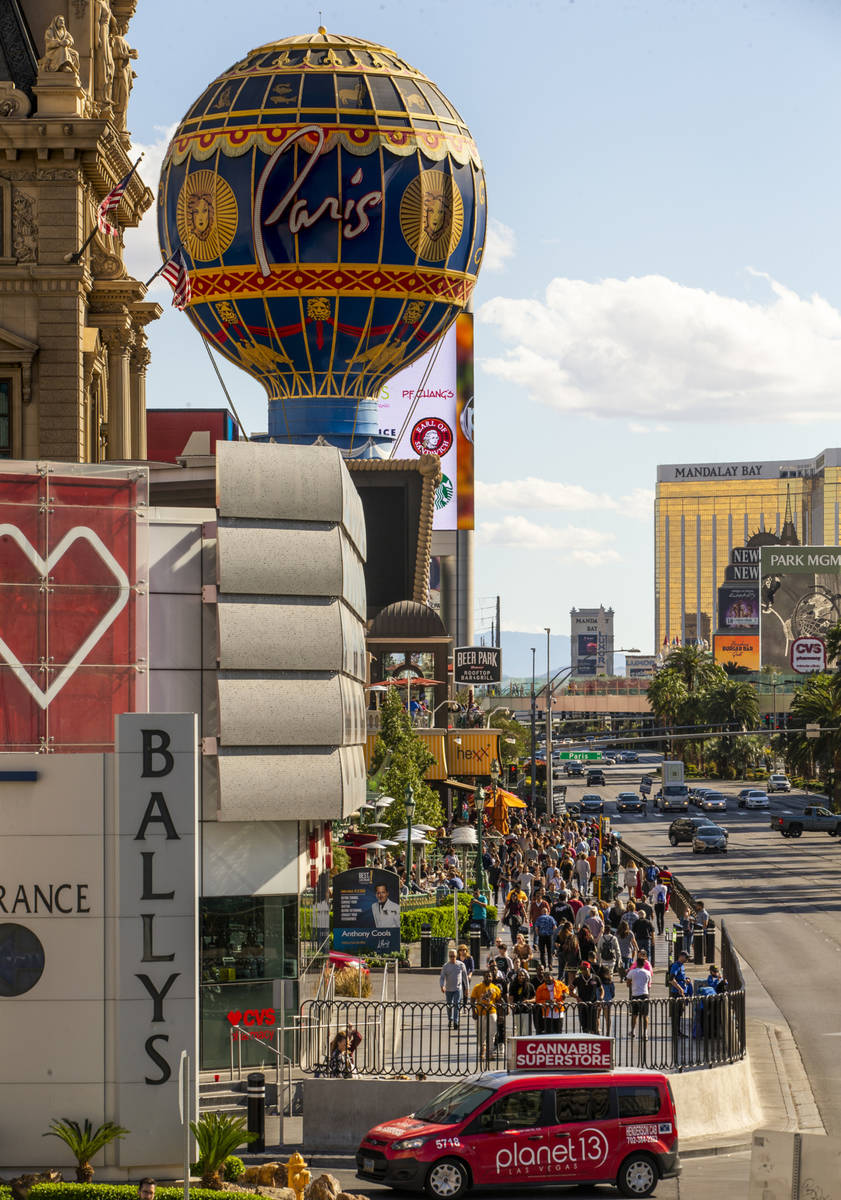 Visitors walk along the Strip near Bally's on Sunday, March 15, 2020 in Las Vegas. (L.E. Baskow ...