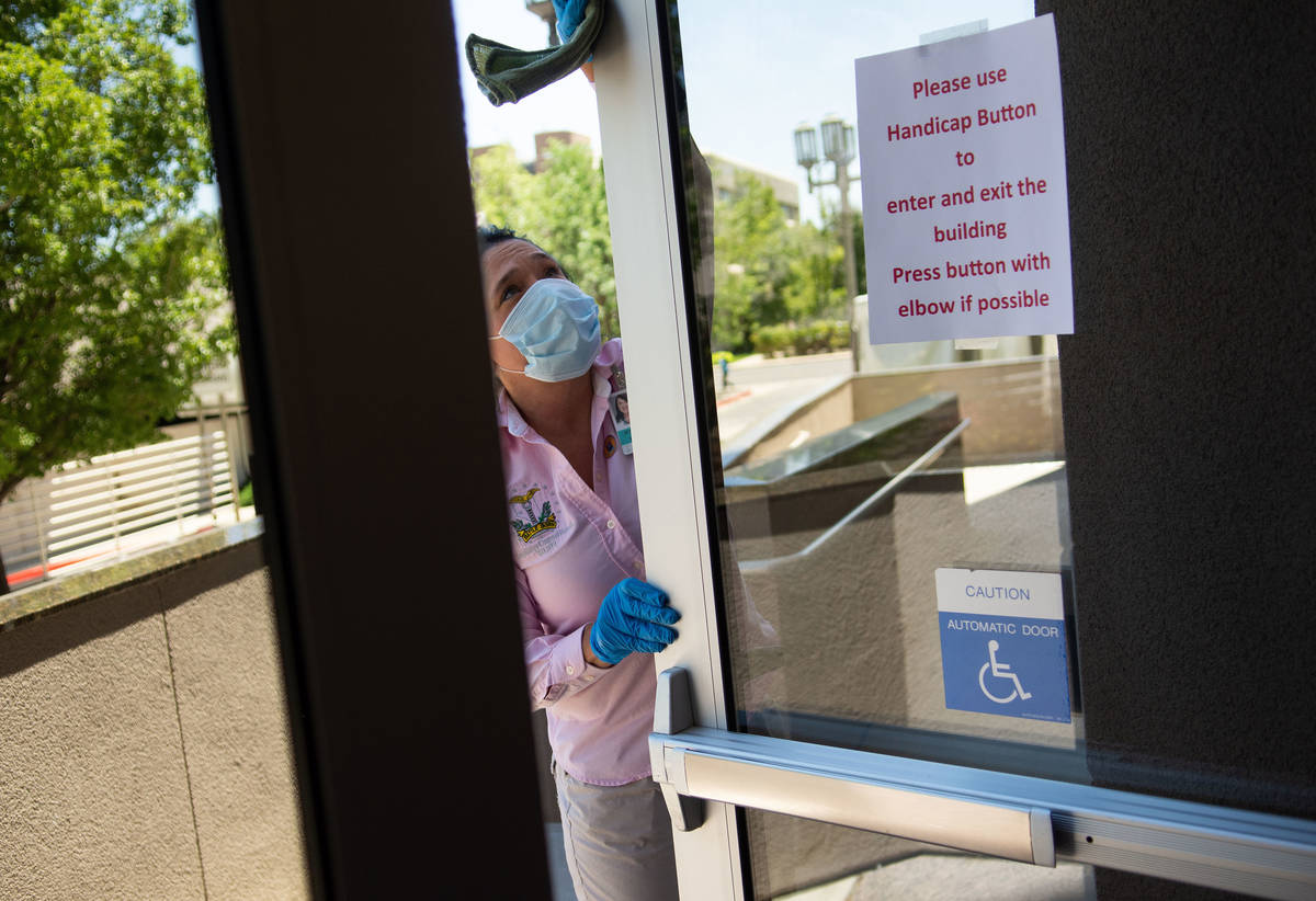 A member of the janitorial staff cleans the entry way on the second day of the 31st Special Ses ...