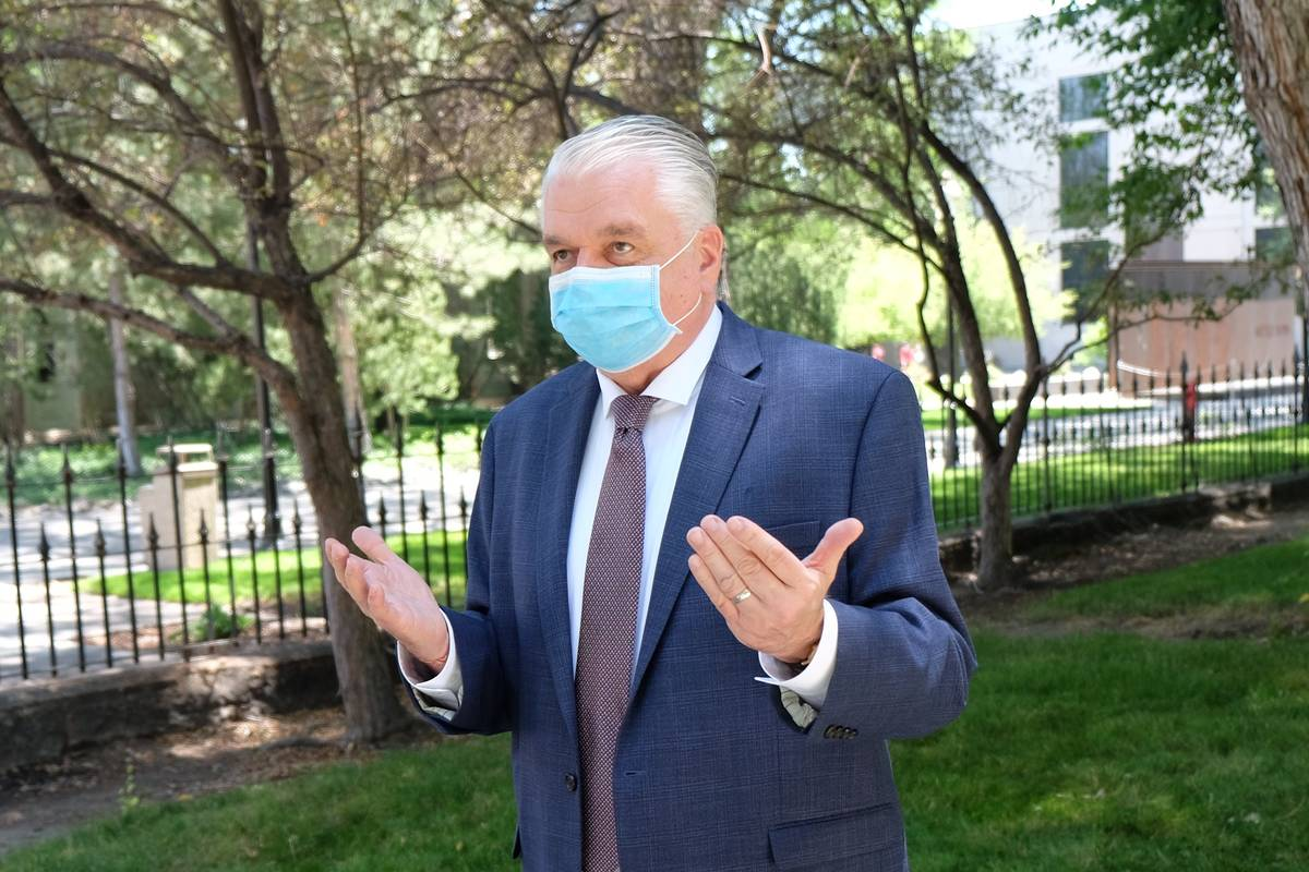 A masked Gov. Steve Sisolak speaks to reporters outside the Capitol Wednesday discussing spendi ...