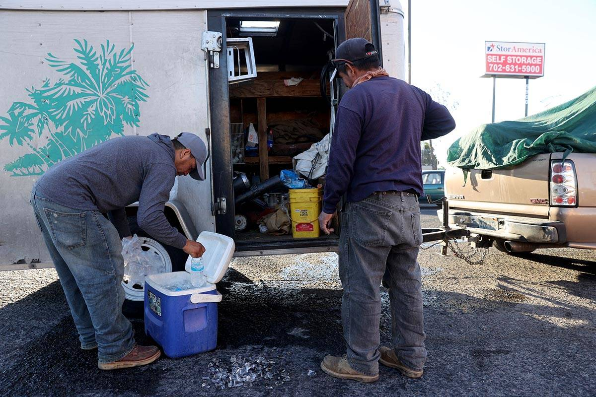 Oscar Orosco, left, Pedro Hernandez load ice for their work day at a kiosk on the corner of Smo ...