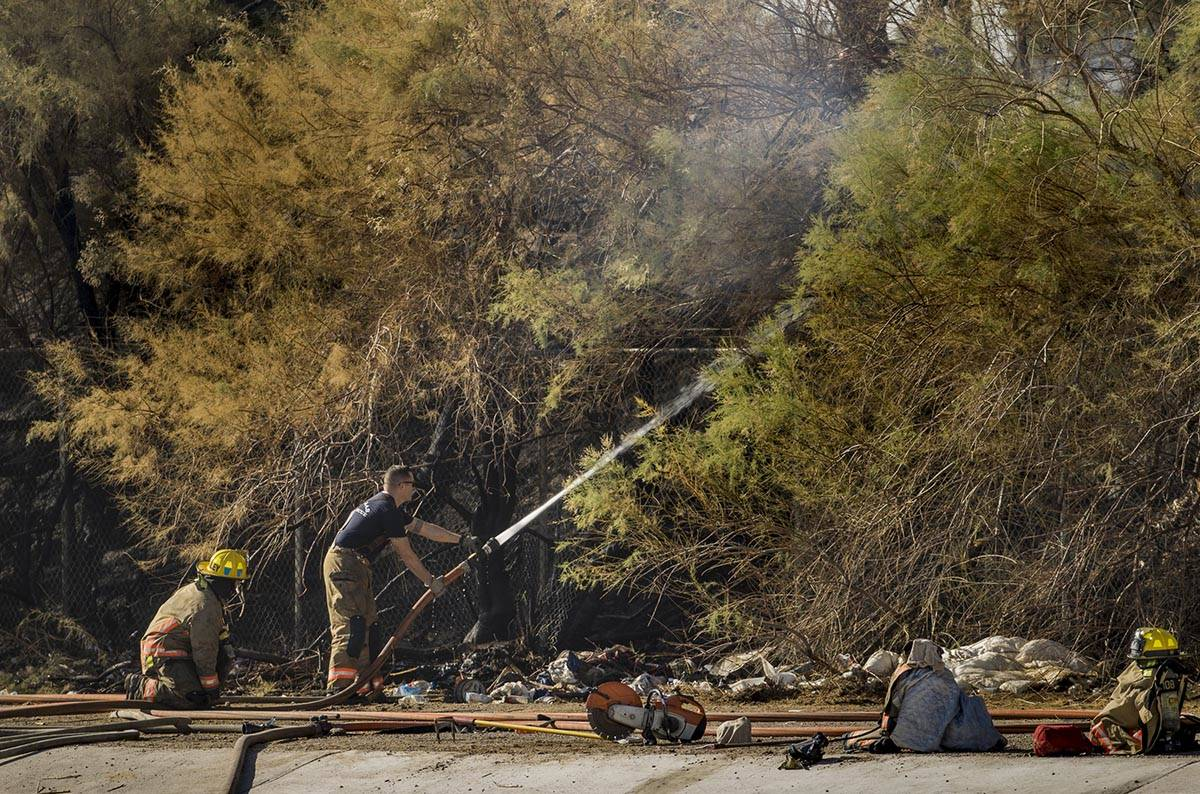 Clark County firefighters extinguish a brush fire in east Las Vegas near the Royal Links Golf C ...