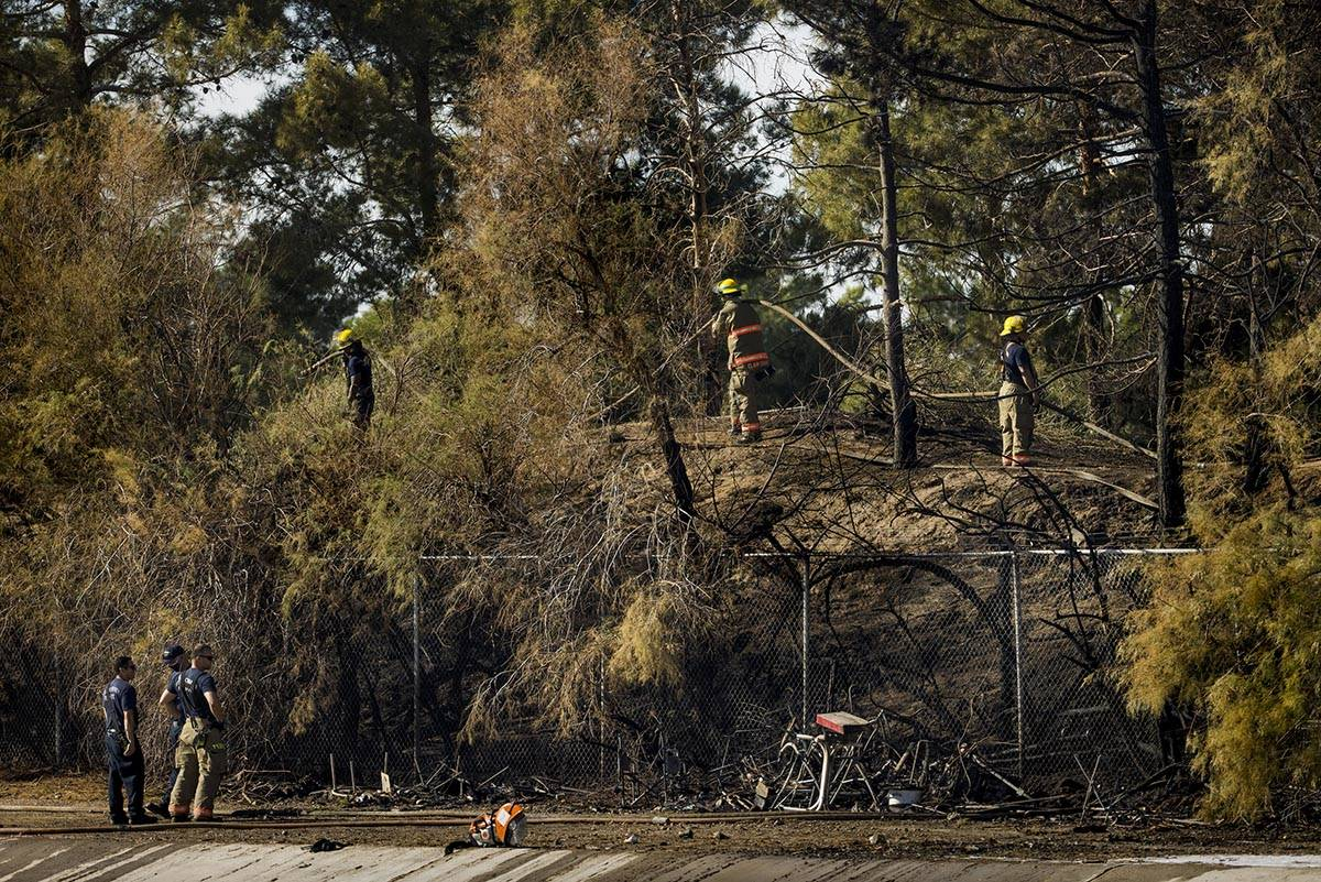A homeless encampment is burned down as Clark County firefighters extinguish a brush fire in ea ...