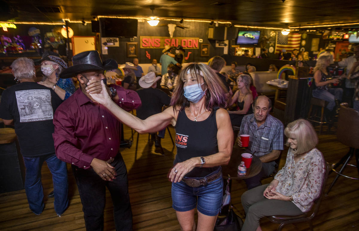 Charles Adams, left, and Debb Saris with Lone Wolf Dancing take to the floor as owner Bobby Kin ...