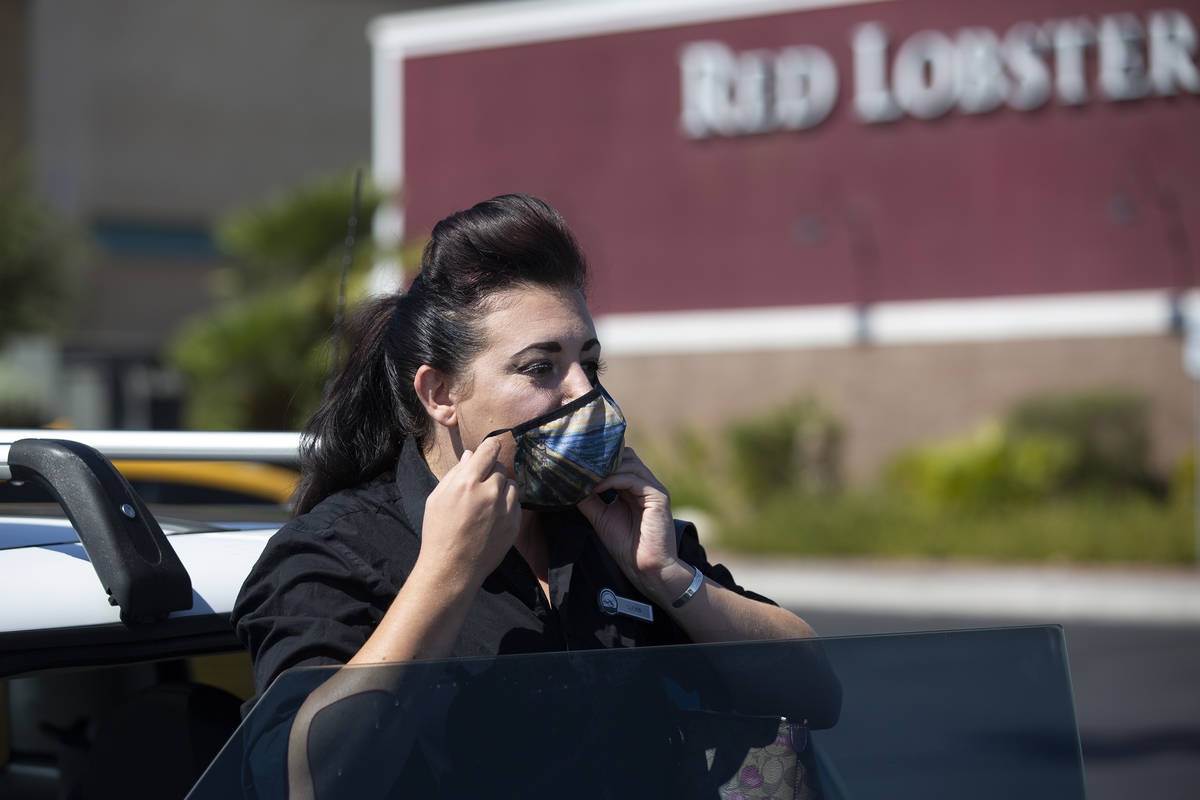 Alexis Cossman puts on her mask before entering work on Tuesday, July 14, 2020, in Las Vegas. C ...