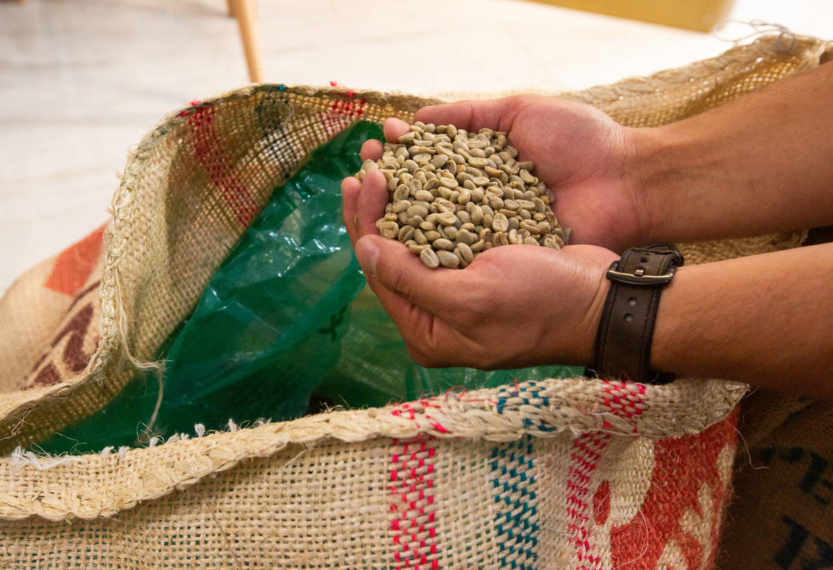 Josh Molina, the owner of Take It Easy, shows one of the types of coffee beans used in the coff ...