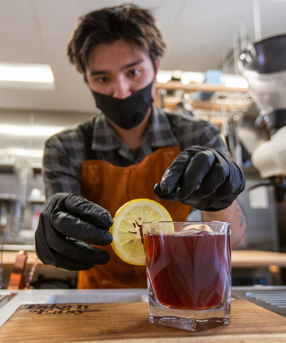 Erik Kelley, a barista at Take It Easy, adds a lemon wheel to the On the Block drink in Las Veg ...
