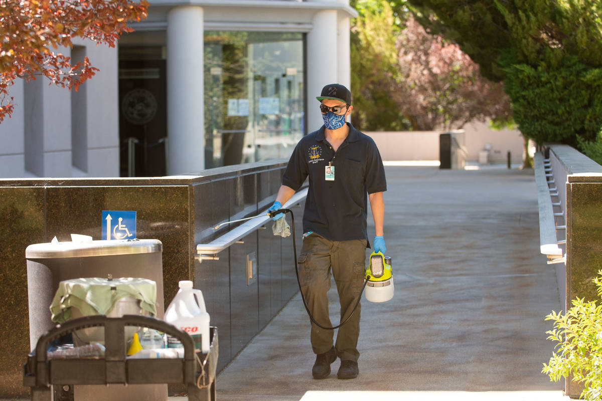 A member of the Legislatures janitorial staff cleans a hadnt railing outside the building on th ...