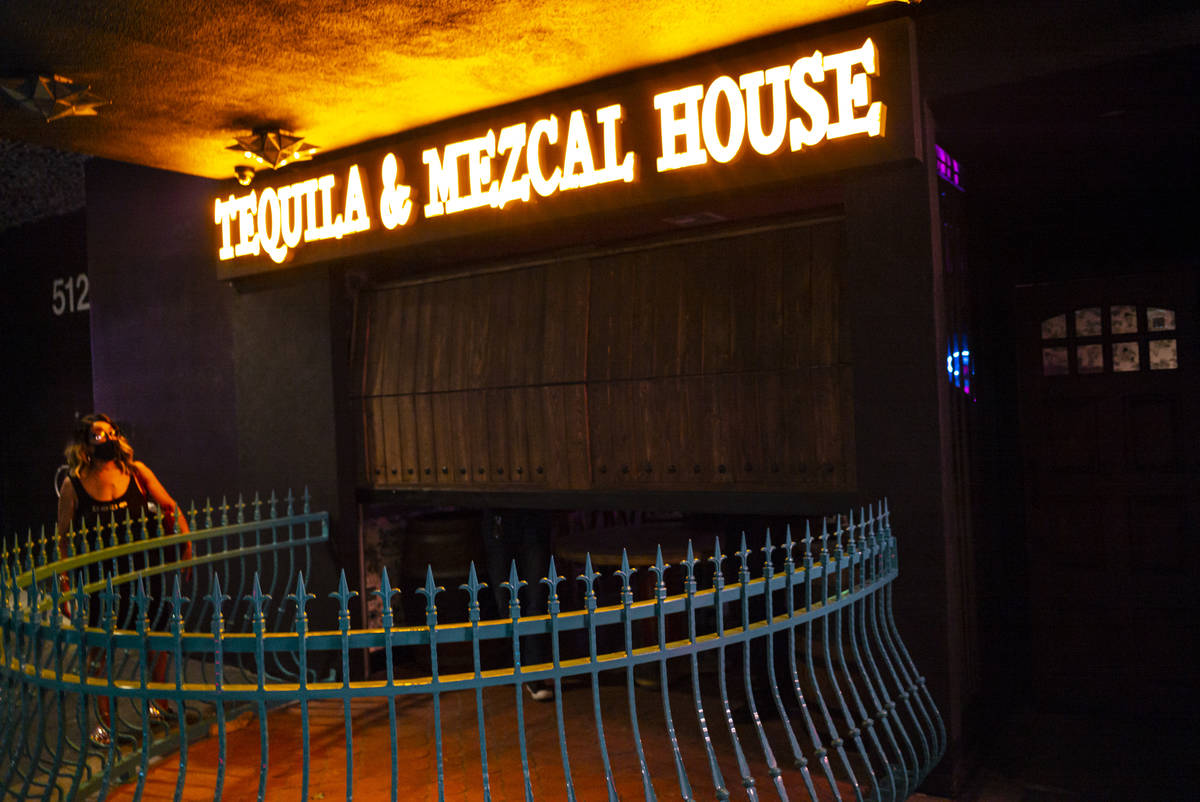 Employees lower the gate at Lucky Day Tequila and & Mezcal House on Fremont Street in downt ...