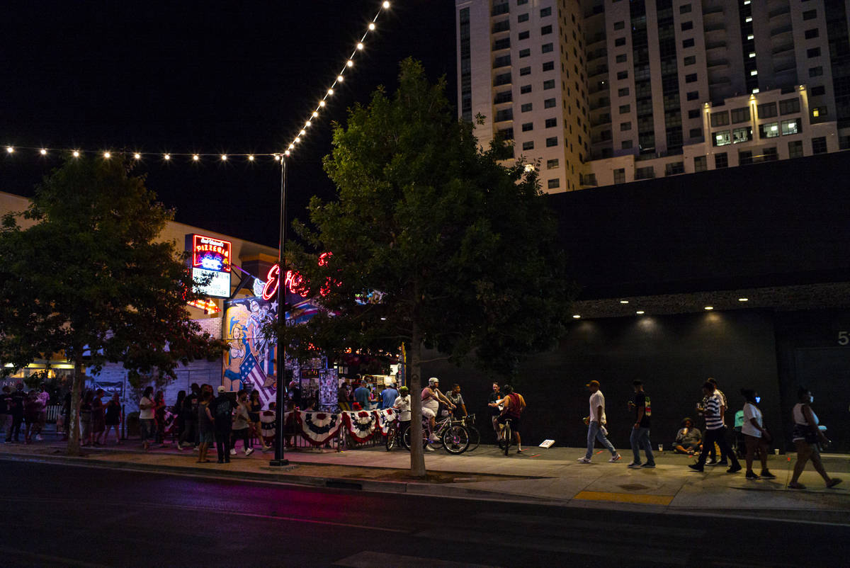 People crowd Fremont Street just after midnight in downtown Las Vegas as bars shut down in Clar ...