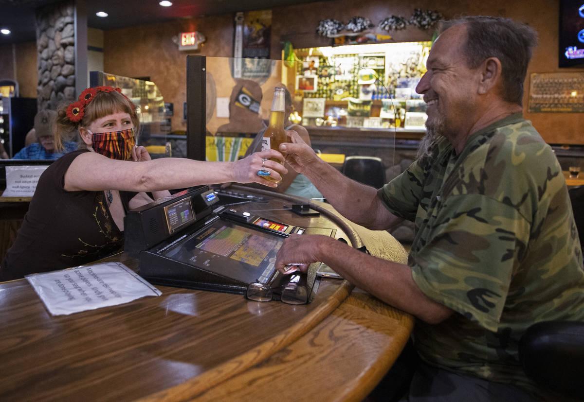 Bartender Teah Heath, left, serves a beer to Lyle Bogggess at Jackson's Bar & Grill ...