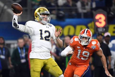 Notre Dame quarterback Ian Book (12) throws a pass under pressure from Clemson safety Tanner Mu ...