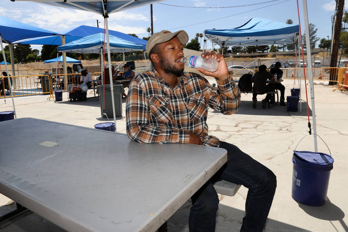 Ronnie Hampton gets a drink of water at the Courtyard Homeless Resource Center cooling station ...