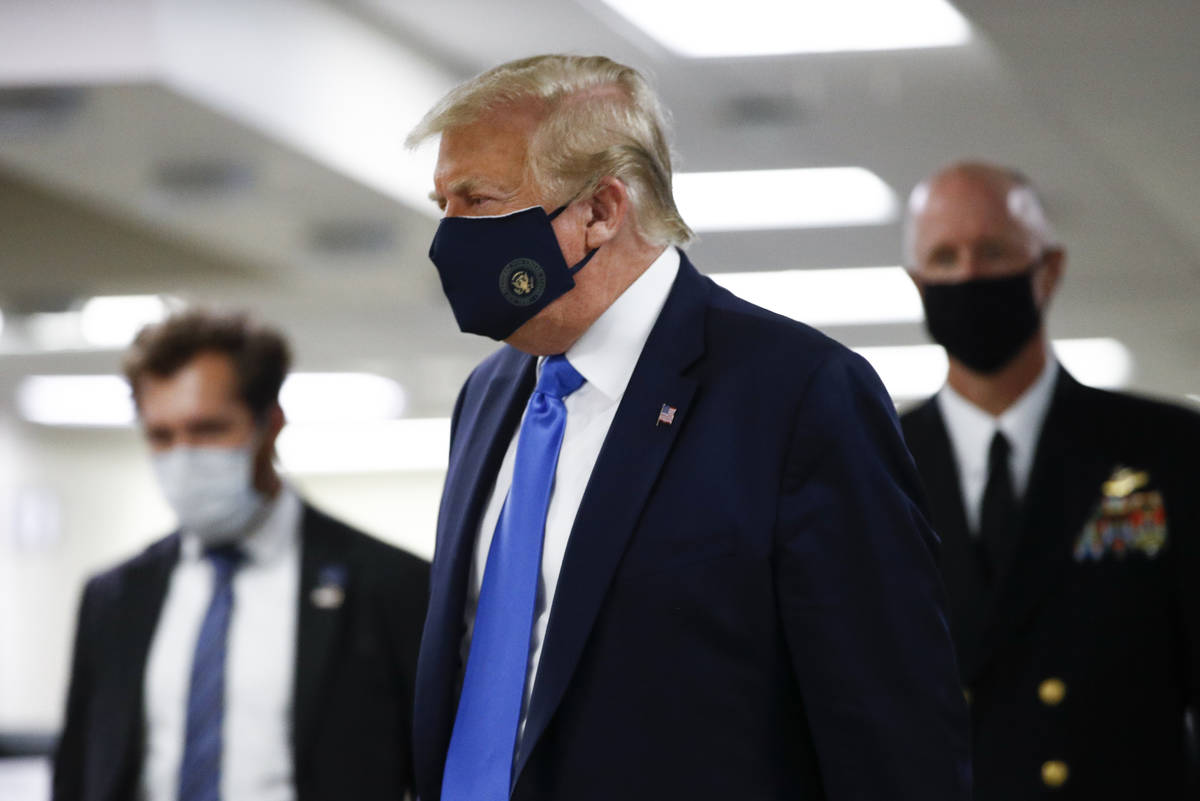 President Donald Trump wears a mask as he walks down the hallway during his visit to Walter Ree ...