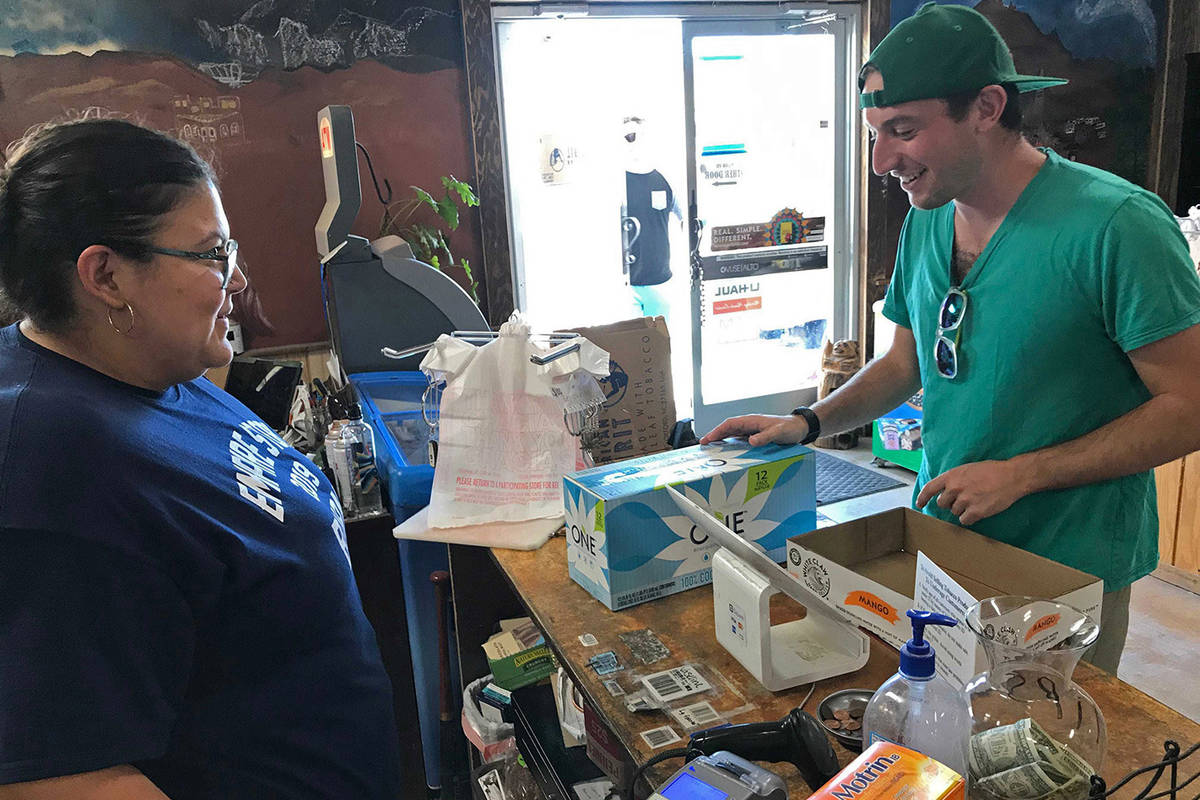 In this photo taken Aug. 25, 2019, Jeremy Keesh, a Burning Man attendee from Chicago, buys coco ...