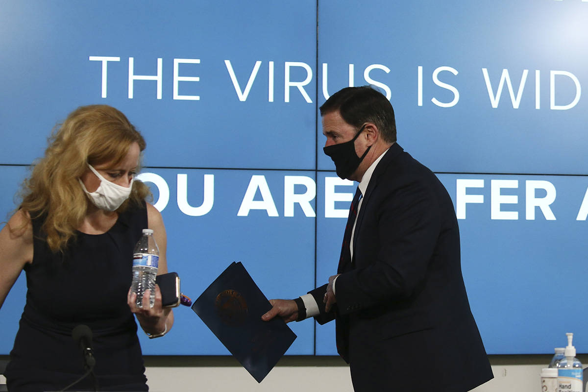 Arizona Republican Gov. Doug Ducey, right, and Dr. Cara Christ, director of the Department of A ...