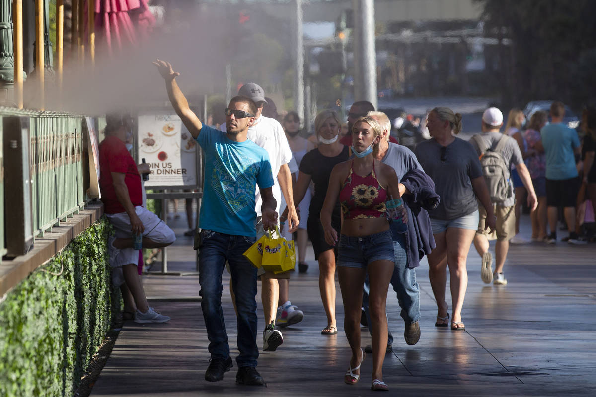Pedestrians feel mist from HEXX kitchen + bar's patio as temperatures peaked to 113 degrees on ...