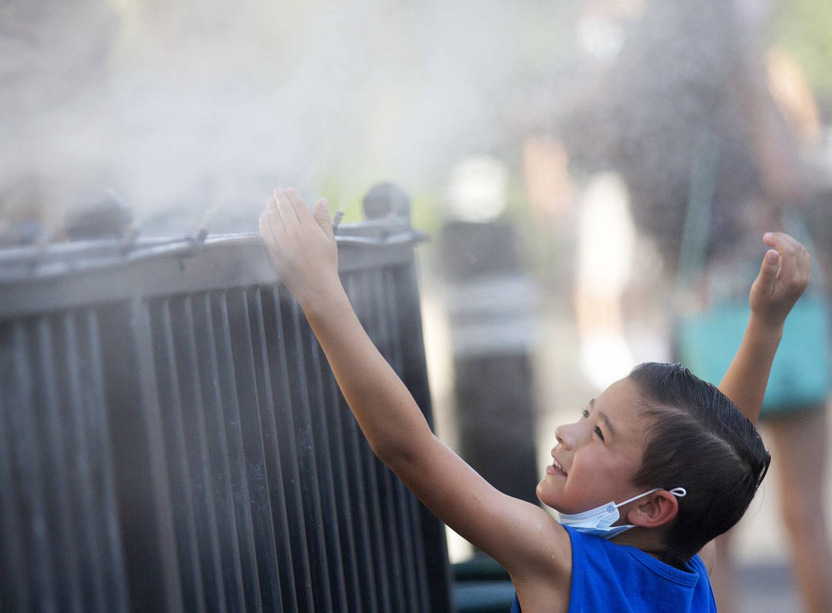 Brody Lester, 5, of California, cools off with the mist from HEXX kitchen + bar's patio as temp ...
