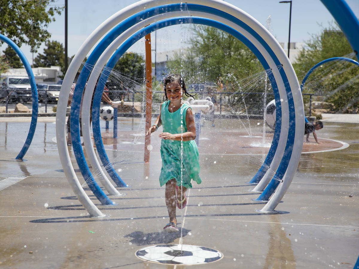 Myriah Vernoy, 8, runs through a water tunnel at Baker Park in Las Vegas, Sunday, July 12, 2020 ...
