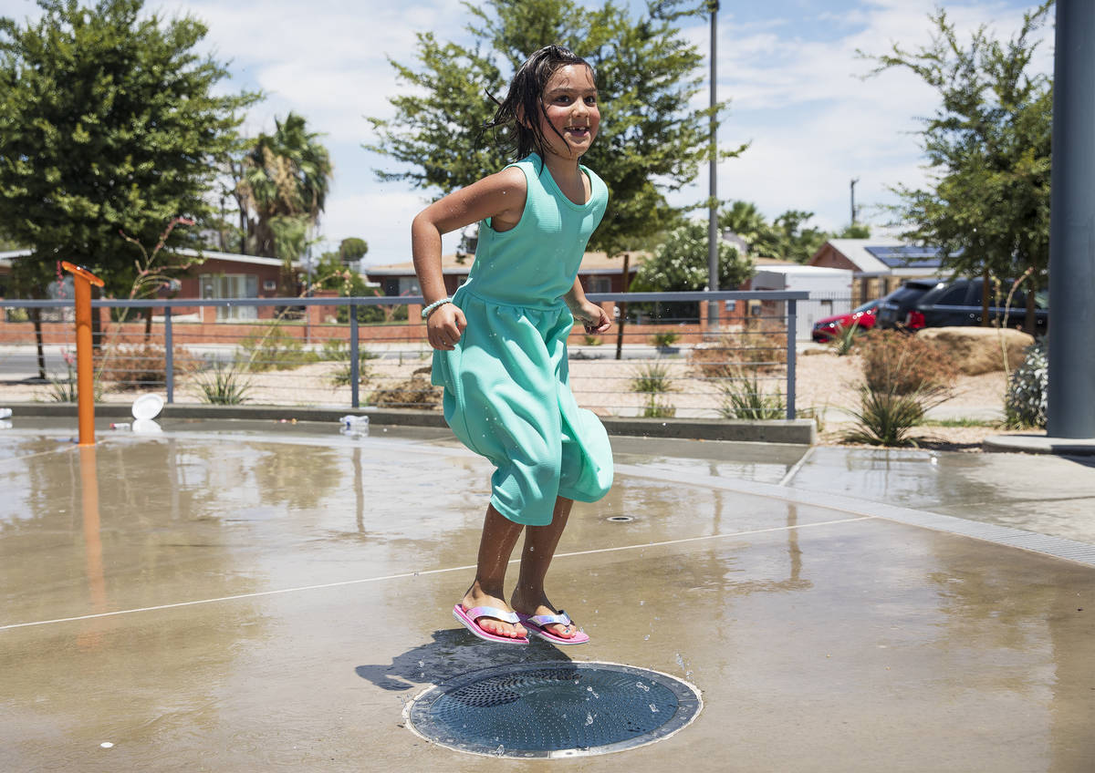 Myriah Vernoy, 8, plays in the water feature at Baker Park in Las Vegas, Sunday, July 12, 2020. ...