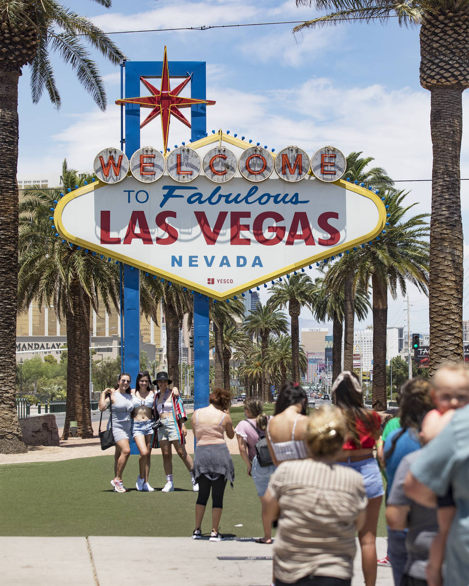 Visitors line up to take a photo at the Fabulous Las Vegas sign in Las Vegas, Sunday, July 12, ...