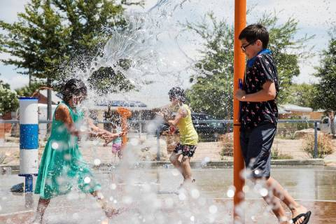 Myriah Vernoy, 8, left, plays with her brother Elysha Vernoy, 14, right, at Baker Park in Las V ...