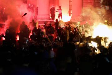 Protesters clash with riot police on the steps of the Serbian parliament during a protest in Be ...