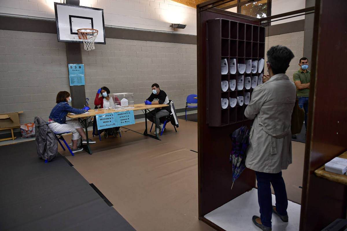 A woman prepares her vote while staff members of a polling station wear face masks to help curb ...