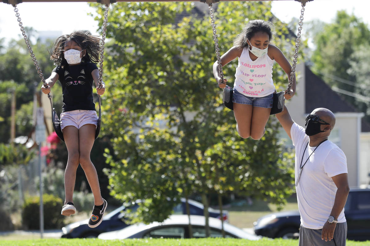 Afework Meshesha, right, pushes his daughter Yohanna while she rides a swing at a playground, S ...