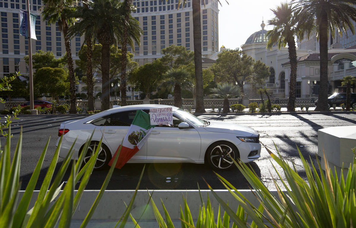 "A car holds a sign saying ""will fight for you Vanessa"" as it drives down Las Vegas Boulevard on ..."
