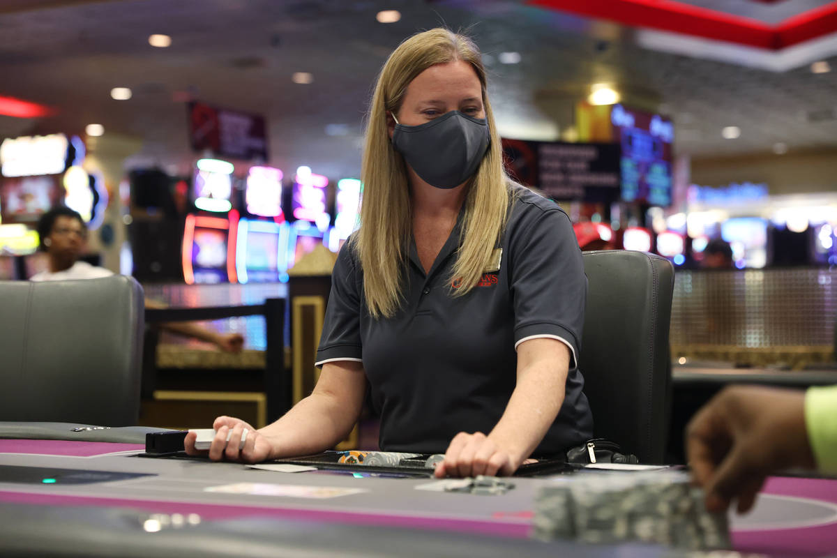 Dealer Joey Pike works a poker table during the first day after reopening at The Orleans hotel- ...