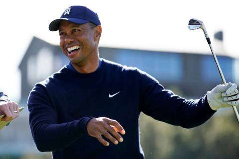 Tiger Woods smiles after hitting his tee shot on the 16th hole during the Genesis Invitational ...