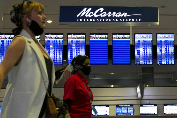 Arriving passengers walk past McCarran International Airport sign on Wednesday, June 24, 2020, ...