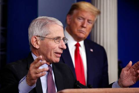 FILE - In this April 22, 2020 file photo, President Donald Trump watches as Dr. Anthony Fauci, ...