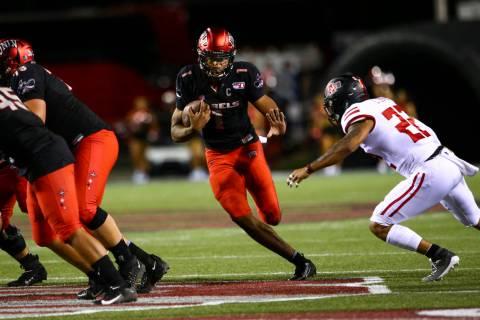 UNLV Rebels quarterback Armani Rogers (1) runs past Arkansas State Red Wolves linebacker Caleb ...