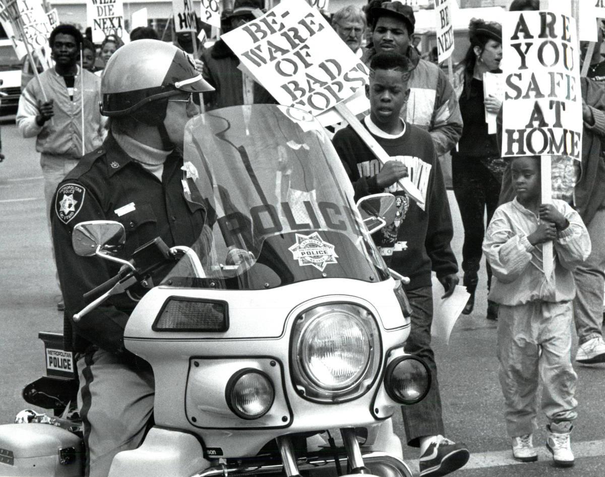 Metropolitan Police Department officers escort marchers protesting Charles Bush's killing durin ...