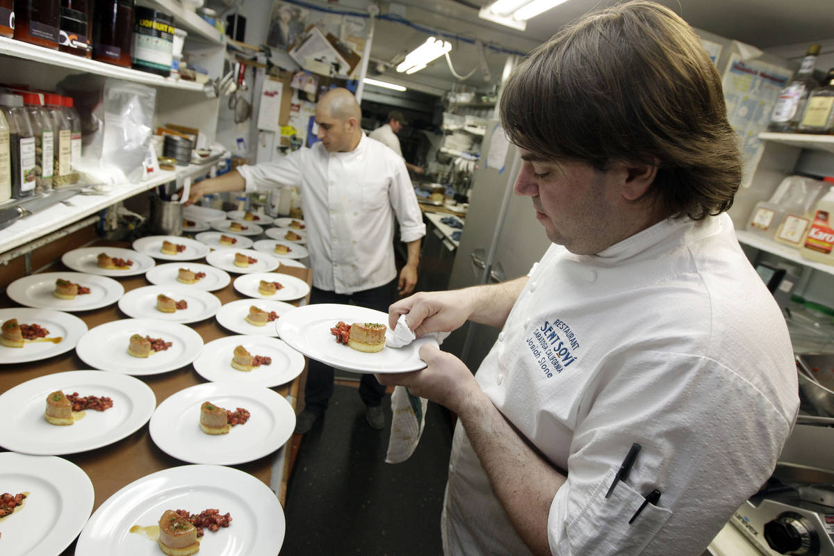 FILE - In this May 11, 2012, file photo, chef and owner Josiah Slone, right, prepares a foie gr ...