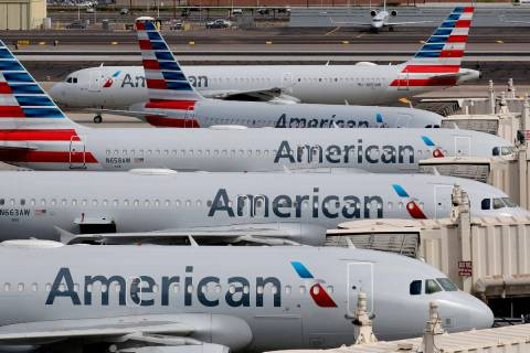 FILE - In this March 25, 2020, file photo, American Airlines jets sit idly at their gates as a ...