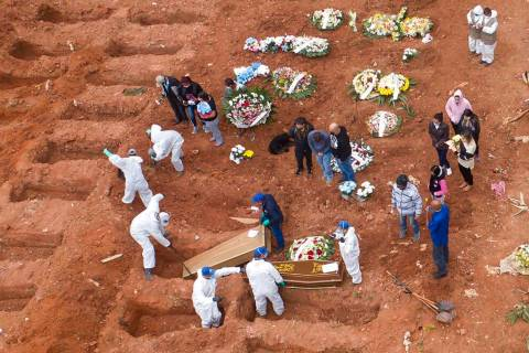 Cemetery workers in protective clothing bury victims of the new coronavirus at the Vila Formosa ...