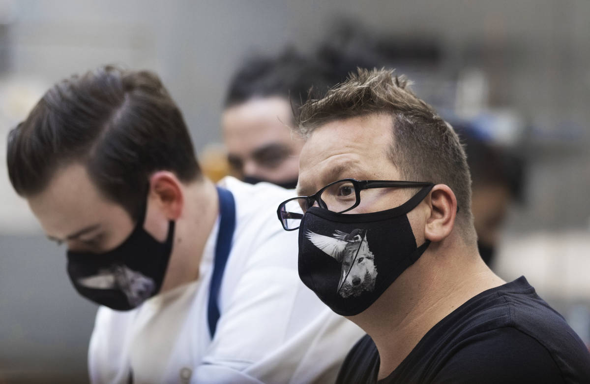 Chef/owner Brian Howard, right, works in the kitchen wearing a custom face mask at Sparrow + Wo ...