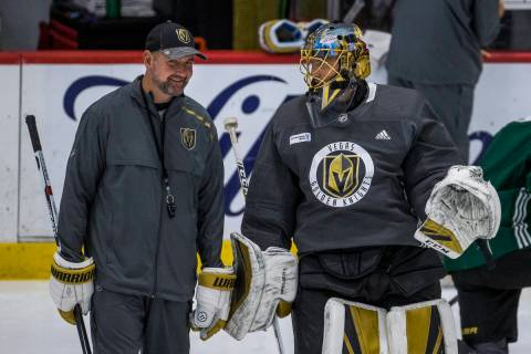 Vegas Golden Knights head coach Peter DeBoer, left, chats on the ice with goaltender Marc-Andre ...