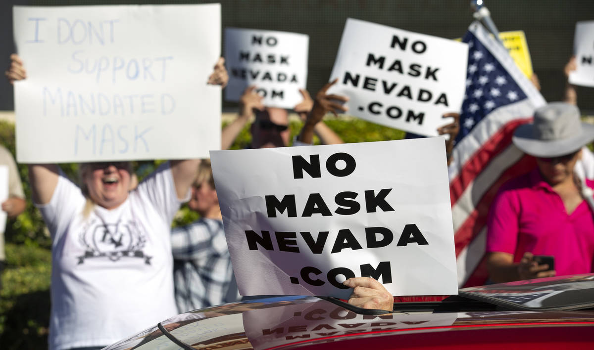 "A passing car supports the ""No Mask Protest"" at the intersection of West Sunset Road ..."