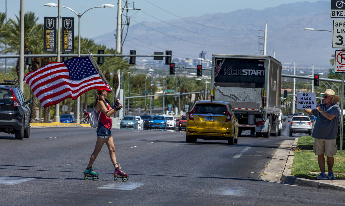 Christy Kettler roller skates with an American flag as others join in a No Mask Nevada PAC rall ...