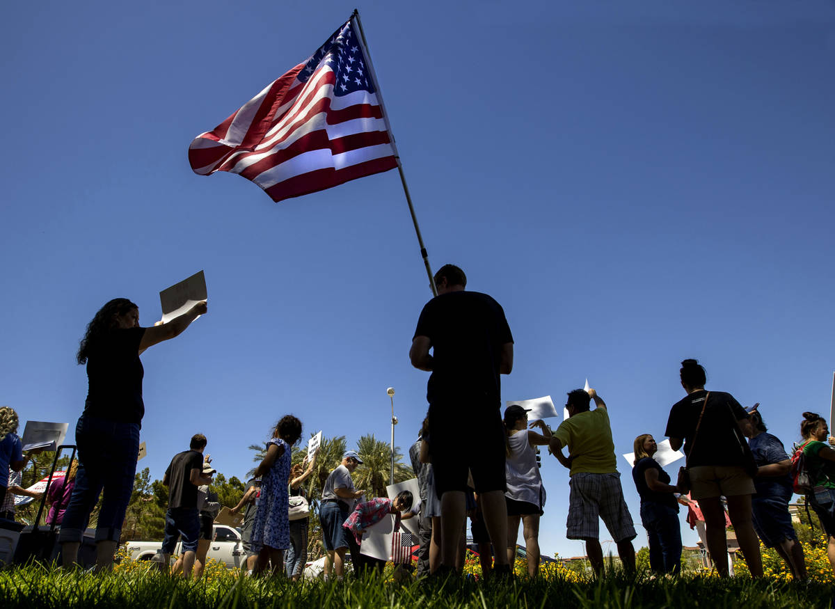 A protester holds an American flag as others wave signs and chant slogans during a No Mask Neva ...