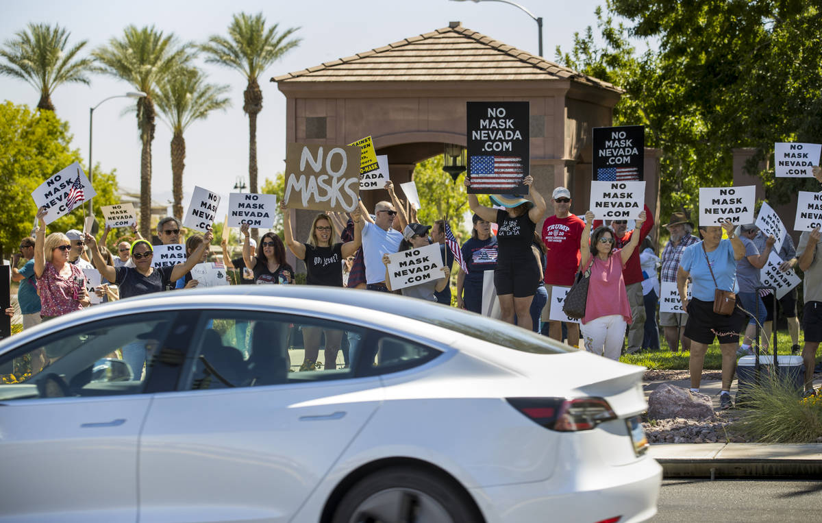 Protesters hold signs and wave to cars during a No Mask Nevada PAC rally along South Green Vall ...