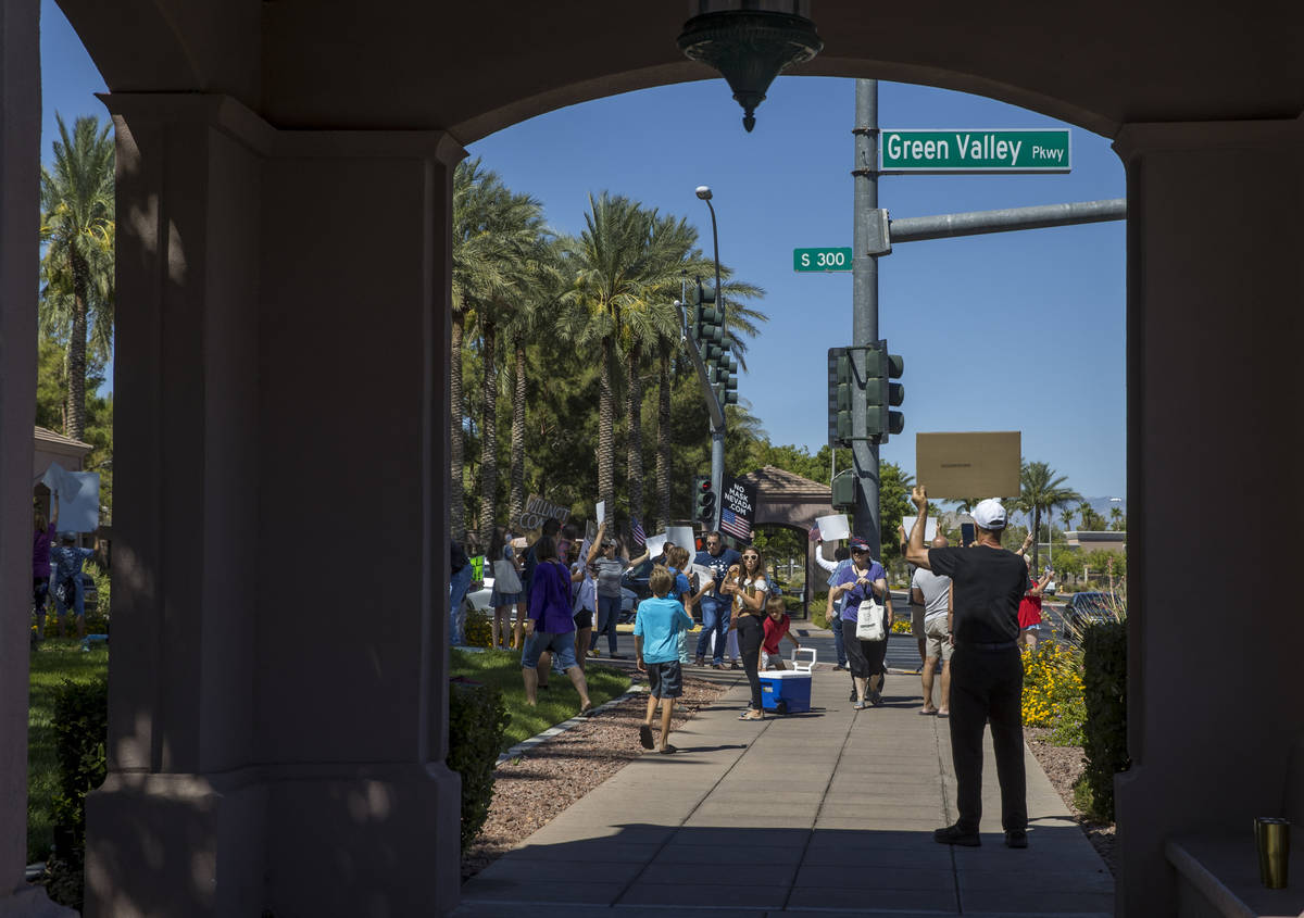 Protesters hold signs and chant slogans during a No Mask Nevada PAC rally along South Green Val ...