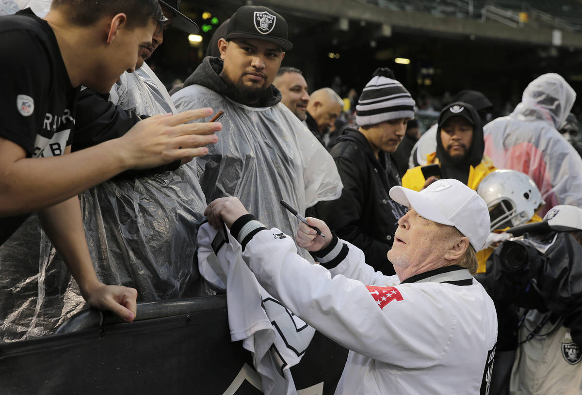 Oakland Raiders owner Mark Davis signs autographs for fans before an NFL football game between ...