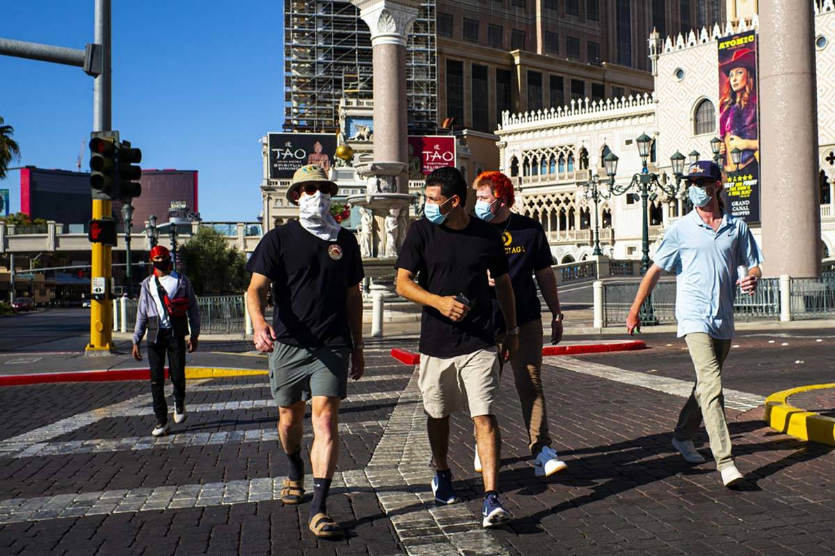 People wearing masks walk along the Las Vegas Strip on Friday, July 17, 2020. (Chase Stevens/La ...