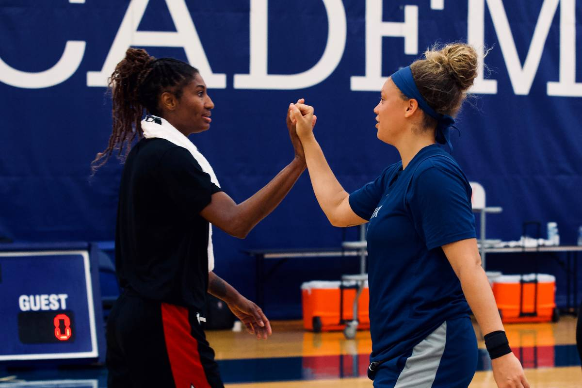 Aces swing player Angel McCoughtry high fives an unidentified Minnesota Lynx player after pract ...